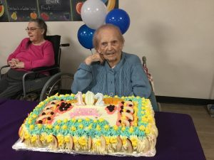 Oliver in front of cake on 102nd birthday